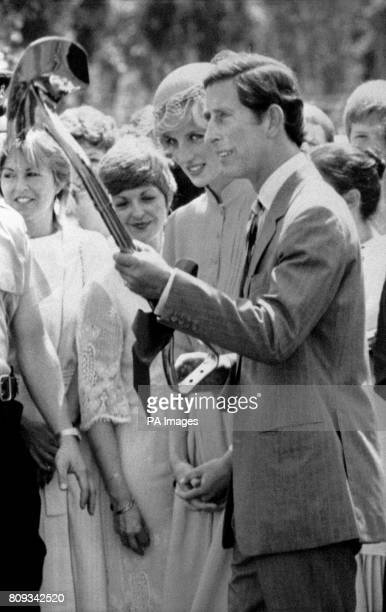 Prince Charles gets the measure of his weapon a shovel held with one hand as he and the Princess of Wales prepare to plant a tree at the Terry Fox...