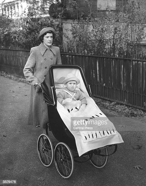 Prince Charles heir to the British throne riding in his pram pushed by his nanny Mabel Anderson