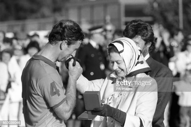 Prince Charles is presented with the runnersup prize by his mother the Queen following his team's defeat in the Silver Jubilee Cup match against...