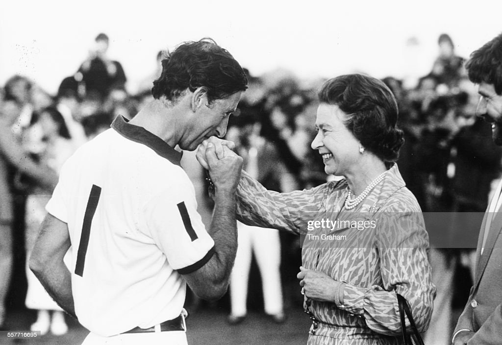 Prince Charles kissing the hand of his smiling mother, HM Queen Elizabeth II, at a polo match, Windsor, England, July 28th 1985.