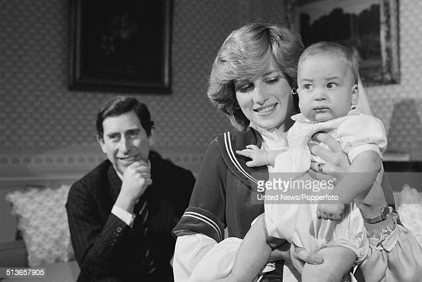 Prince Charles looks on as Diana Princess of Wales holds their baby son Prince William at Kensington Palace in London on 22nd December 1982