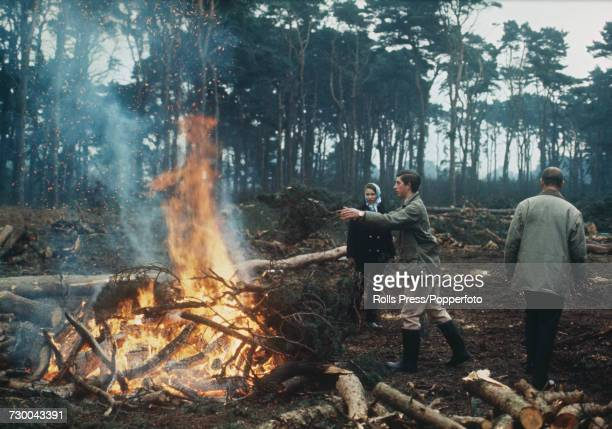 Prince Charles pictured placing branches on a bonfire as his sister Princess Anne looks on and his father Prince Philip Duke of Edinburgh walks off...