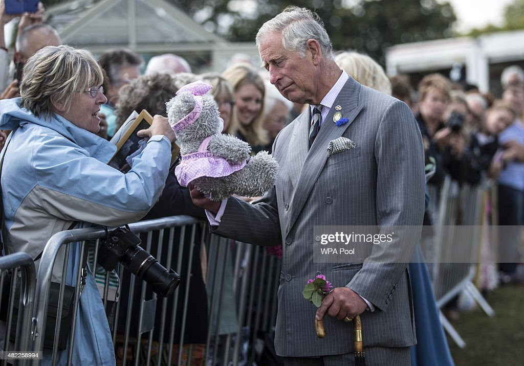 Prince Charles Prince of Wales accepts a toy teddy bear for his new grandaughter Princess Charlotte presented to him by Sheila Clark from Glasgow as...