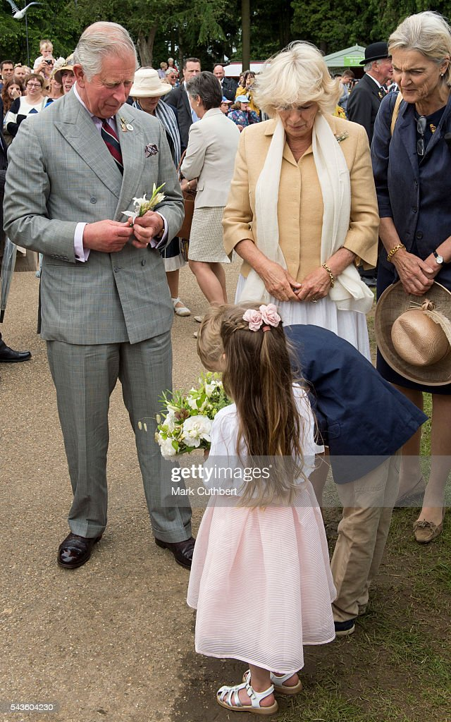 Prince Charles, Prince of Wales and Camilla, Duchess of Cornwall are presented with flowers by two chldren during their visit to The Royal Norfolk Show at Norfolk Showground on June 29, 2016 in Norwich, England.