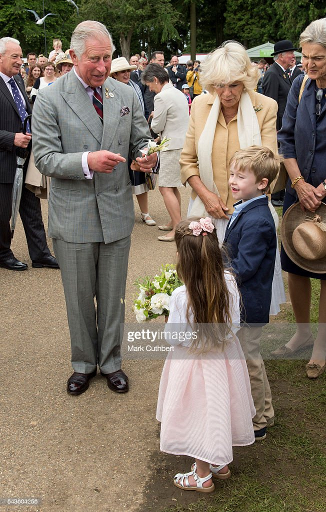<a gi-track='captionPersonalityLinkClicked' href=/galleries/search?phrase=Prince+Charles+-+Prince+of+Wales&family=editorial&specificpeople=160180 ng-click='$event.stopPropagation()'>Prince Charles</a>, Prince of Wales and <a gi-track='captionPersonalityLinkClicked' href=/galleries/search?phrase=Camilla+-+Duchess+of+Cornwall&family=editorial&specificpeople=158157 ng-click='$event.stopPropagation()'>Camilla</a>, Duchess of Cornwall are presented with flowers by two chldren during their visit to The Royal Norfolk Show at Norfolk Showground on June 29, 2016 in Norwich, England.