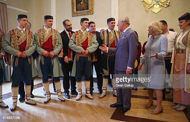 Prince Charles Prince of Wales and Camilla Duchess of Cornwall chat with members of a Montenegran folk dance ensemble after a performance at a...