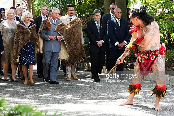 Prince Charles Prince of Wales and Camilla Duchess of Cornwall dressed in Korowai are greeted by a Maori warrior during a visit to Turangawaewae...