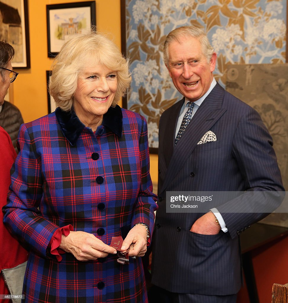 Prince Charles Prince of Wales and Camilla Duchess of Cornwall laugh at a piece of gold tool embossing the Duchess created during a visit to the Art...