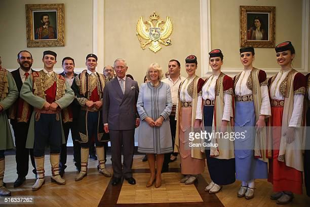 Prince Charles Prince of Wales and Camilla Duchess of Cornwall pause for a photo with members of a Montenegran folk dance ensemble after a...