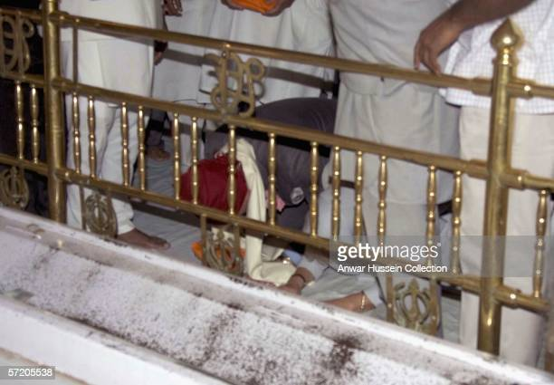 Prince Charles Prince of Wales and Camilla Duchess of Cornwall pray as they visit the Anadpur Sahib Gurdwara on the eighth day of a 12 day official...