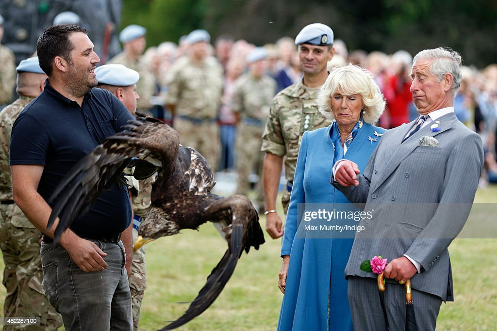 Prince Charles, Prince of Wales and Camilla, Duchess of Cornwall react as Zephyr, a Bald Eagle, and mascot of The Army Air Corps flaps it's wings as they visit the Sandringham Flower Show on July 29, 2015 in King's Lynn, England.