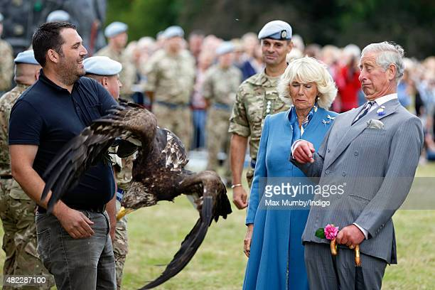 Prince Charles Prince of Wales and Camilla Duchess of Cornwall react as Zephyr a Bald Eagle and mascot of The Army Air Corps flaps it's wings as they...