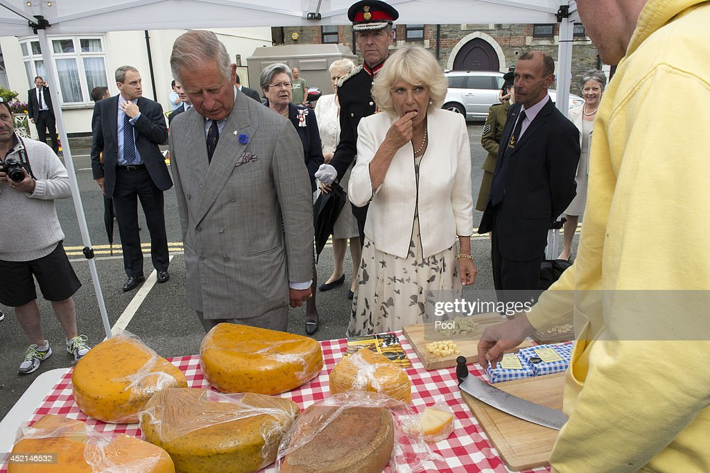 Prince Charles, Prince of Wales and Camilla, Duchess of Cornwall sample cheese as they visit Looe Market on July 14, 2014 in Looe, England.