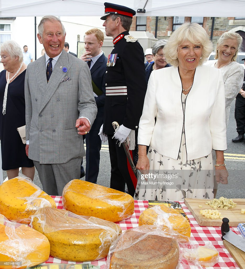 <a gi-track='captionPersonalityLinkClicked' href=/galleries/search?phrase=Prince+Charles&family=editorial&specificpeople=160180 ng-click='$event.stopPropagation()'>Prince Charles</a>, Prince of Wales and <a gi-track='captionPersonalityLinkClicked' href=/galleries/search?phrase=Camilla+-+Duchess+of+Cornwall&family=editorial&specificpeople=158157 ng-click='$event.stopPropagation()'>Camilla</a>, Duchess of Cornwall sample some cheese as they tour a market on day one of their annual visit to Devon and Cornwall on July 14, 2014 in Looe, England.
