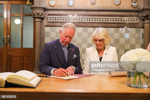Prince Charles Prince of Wales and Camilla Duchess of Cornwall sign a book of condolence after a reception in Manchester Town Hall to thank those...