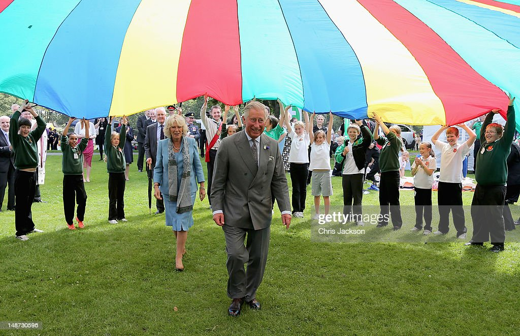Prince Charles, Prince of Wales and Camilla, Duchess of Cornwall take part in a Youth Showcase 'Parachute game' during a visit to Saumarez Park on July 19, 2012 in St Peter's Port, United Kingdom. The Prince of Wales and the Duchess of Cornwall are in Jersey as part of a Diamond Jubilee visit to the Channel Islands taking in Jersey, Guernsey and Sark.