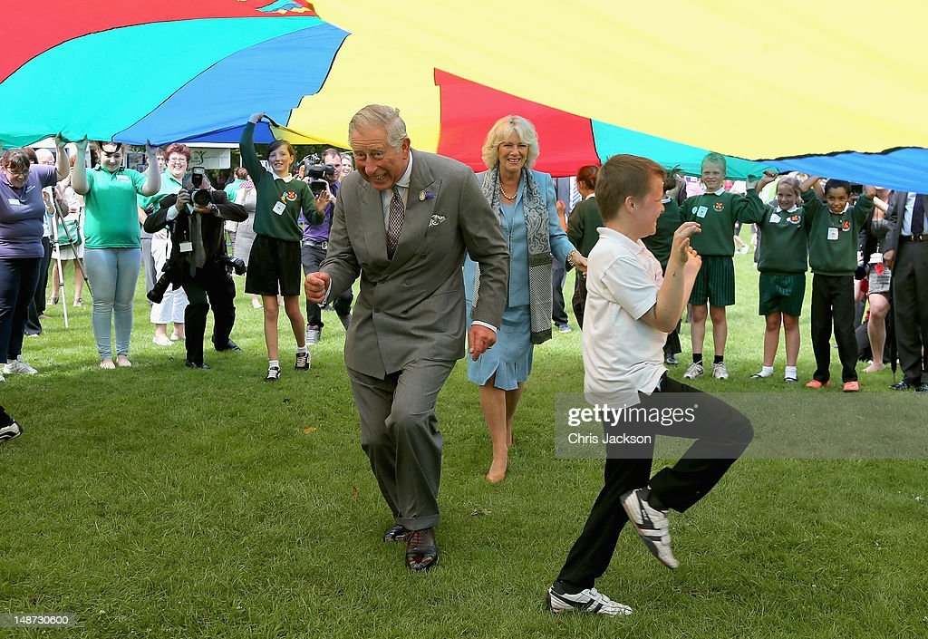 <a gi-track='captionPersonalityLinkClicked' href=/galleries/search?phrase=Prince+Charles&family=editorial&specificpeople=160180 ng-click='$event.stopPropagation()'>Prince Charles</a>, Prince of Wales and <a gi-track='captionPersonalityLinkClicked' href=/galleries/search?phrase=Camilla+-+Duchess+of+Cornwall&family=editorial&specificpeople=158157 ng-click='$event.stopPropagation()'>Camilla</a>, Duchess of Cornwall take part in a Youth Showcase 'Parachute game' during a visit to Saumarez Park on July 19, 2012 in St Peter's Port, United Kingdom. The Prince of Wales and the Duchess of Cornwall are in Jersey as part of a Diamond Jubilee visit to the Channel Islands taking in Jersey, Guernsey and Sark.