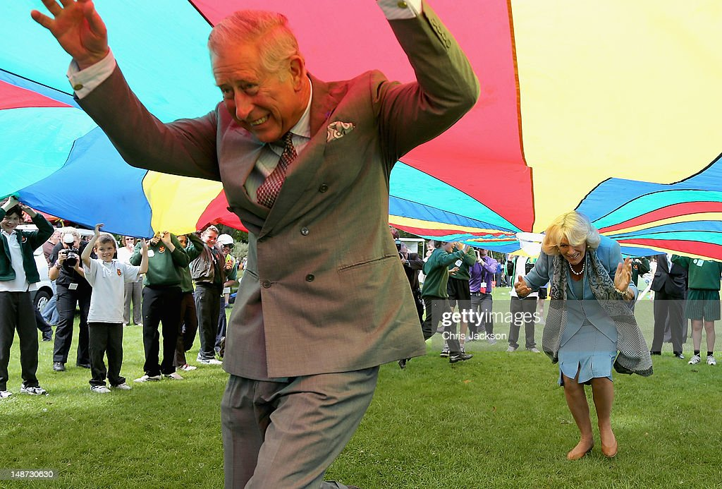 Prince Charles, Prince of Wales and <a gi-track='captionPersonalityLinkClicked' href=/galleries/search?phrase=Camilla+-+Duquesa+da+Cornualha&family=editorial&specificpeople=158157 ng-click='$event.stopPropagation()'>Camilla</a>, Duchess of Cornwall take part in a Youth Showcase 'Parachute game' during a visit to Saumarez Park on July 19, 2012 in St Peter's Port, United Kingdom. The Prince of Wales and the Duchess of Cornwall are in Jersey as part of a Diamond Jubilee visit to the Channel Islands taking in Jersey, Guernsey and Sark.
