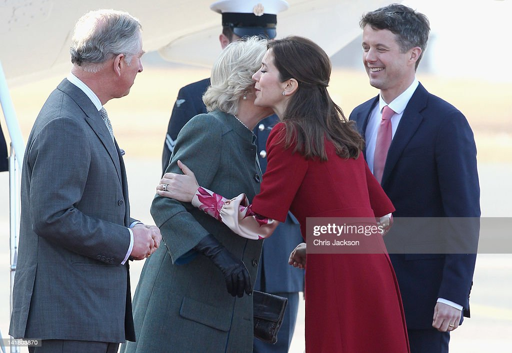 Prince Charles, Prince of Wales and Crown Prince Frederik Of Denmark look on as Camilla, Duchess of Cornwall kisses Princess Mary of Denmark as they arrives at Copenhagen Kastrup Airport on March 24, 2012 in Copenhagen, Denmark. Prince Charles, Prince of Wales and Camilla, Duchess of Cornwall are on a Diamond Jubilee tour of Scandinavia that takes in Norway, Sweden and Denmark.
