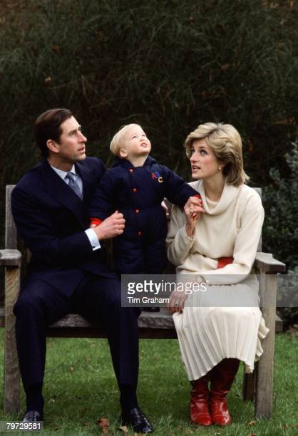 Prince Charles Prince of Wales and Diana Princess of Wales sit on a bench for with their son Prince William in the garden at Kensington Palace
