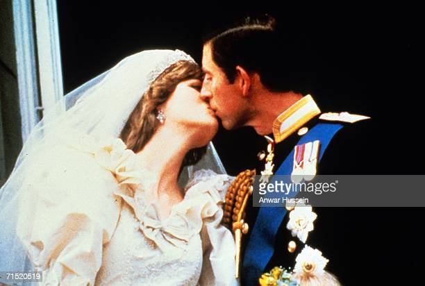 Prince Charles Prince of Wales kisses Diana Princess of Wales on the balcony of Buckingham Palace following their wedding July 29 1981 in London...