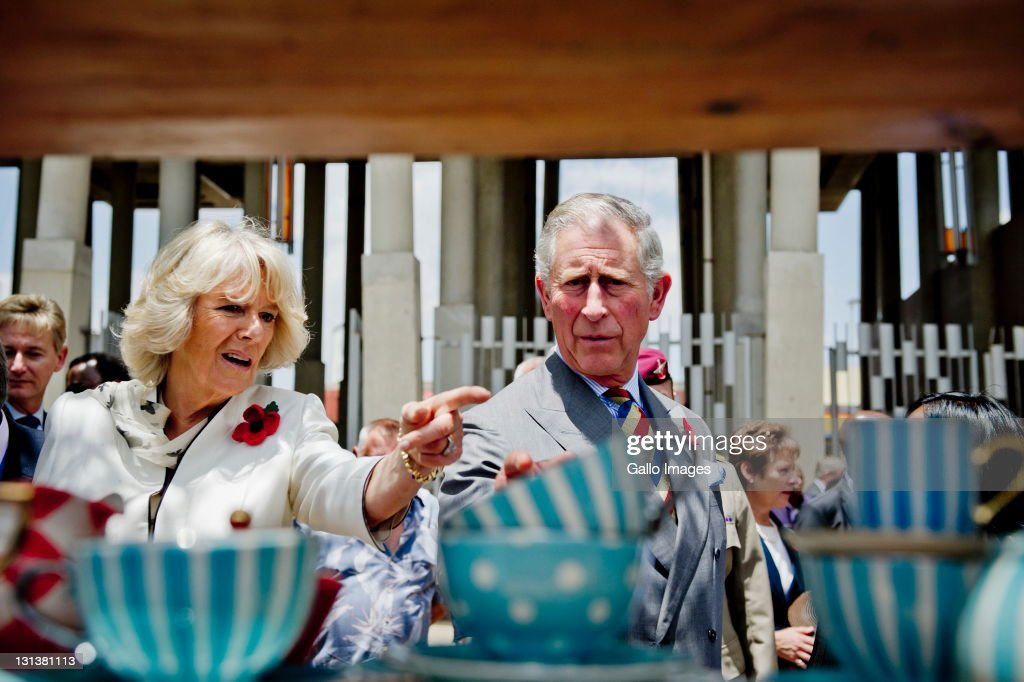 Prince Charles, Prince of Wales and his wife <a gi-track='captionPersonalityLinkClicked' href=/galleries/search?phrase=Camilla+-+Hertogin+van+Cornwall&family=editorial&specificpeople=158157 ng-click='$event.stopPropagation()'>Camilla</a>, Duchess of Cornwall admire some crockery while visiting a township on November 3, 2011 in Soweto, South Africa. The Prince and Duchess are visiting South Africa as part of the Commonwealth tour.