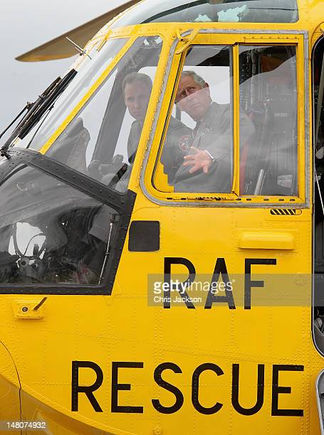 Prince Charles Prince of Wales and Prince William Duke of Cambridge look around an RAF Sea King Rescue helicopter at RAF Valley on July 9 2012 in...