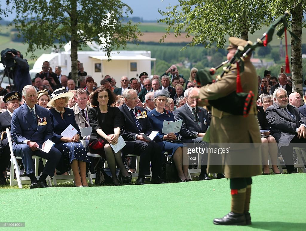 Prince Charles, Prince of Wales, Camilla, Duchess of Cornwall and Northern Ireland Secretary Theresa Villiers join guests watching a piper play at the Ulster Memorial Tower during a service to mark the 100th anniversary of the start of the battle of the Somme on July 1, 2016 in Thiepval, France. The event is part of the Commemoration of the Centenary of the Battle of the Somme at the Commonwealth War Graves Commission Thiepval Memorial in Thiepval, France, where 70,000 British and Commonwealth soldiers with no known grave are commemorated.