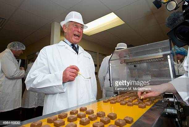 Prince Charles Prince of Wales decorates chocolates during an official visit to 'The House of Dorchester' chocolate factory on November 23 2015 in...