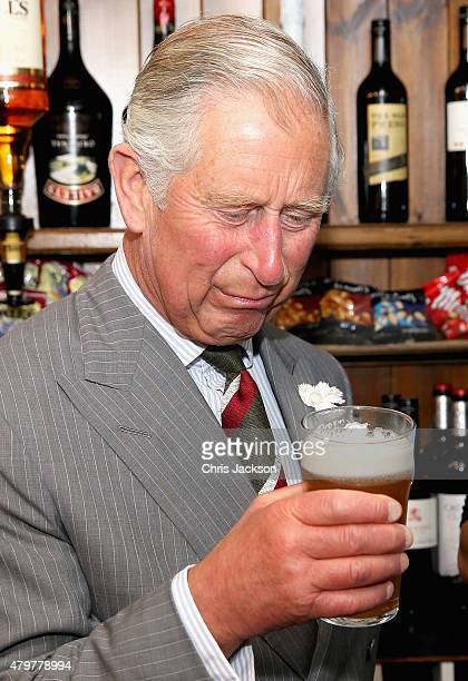 Prince Charles Prince of Wales drinks a pint of 'Prince of Pales' during a visit to the Communityrun Raven Inn Pub on July 7 2015 in Llanarmon yn Lal...