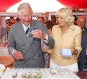 Prince Charles Prince of Wales eats an oyster as Camilla Duchess of Cornwall looks on during their visit to the Whitstable Oyster Festival on July 29...