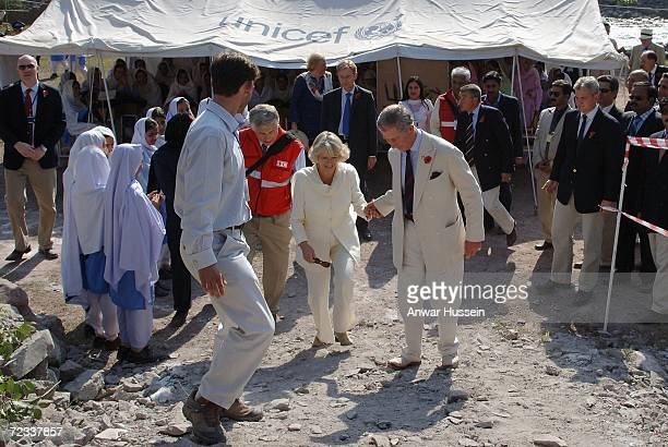 Prince Charles Prince of Wales gives Camilla Duchess of Cornwall a helping hand as they walk through the earthquake devastated village of Pattika...