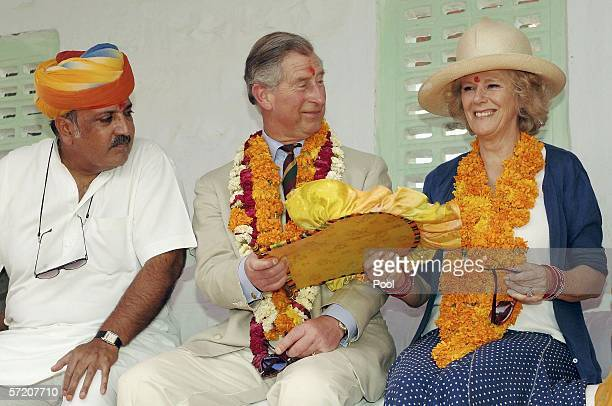 Prince Charles Prince of Wales hand over a fan to his wife Camilla Duchess of Cornwall during their visit to Artiya Village on the tenth day of their...