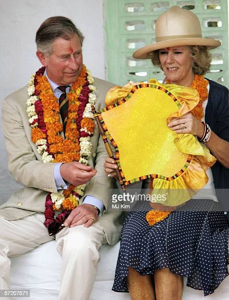Prince Charles Prince of Wales hands over a fan to his wife Camilla Duchess of Cornwall during their visit to Artiya Village on the tenth day of...