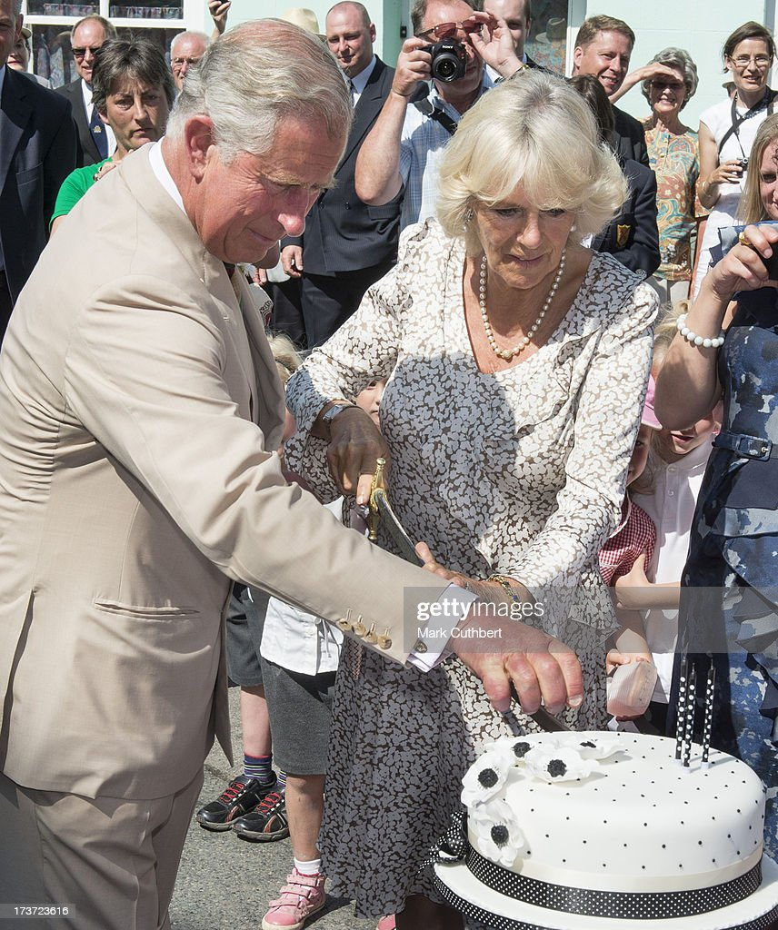 Prince Charles, Prince of Wales helps <a gi-track='captionPersonalityLinkClicked' href=/galleries/search?phrase=Camilla+-+Hertiginna+av+Cornwall&family=editorial&specificpeople=158157 ng-click='$event.stopPropagation()'>Camilla</a>, Duchess of Cornwall, to cut a birthday cake on her 66th birthday, during a walkabout on a visit to Lostwithiel on July 17, 2013 in Cornwall, England.