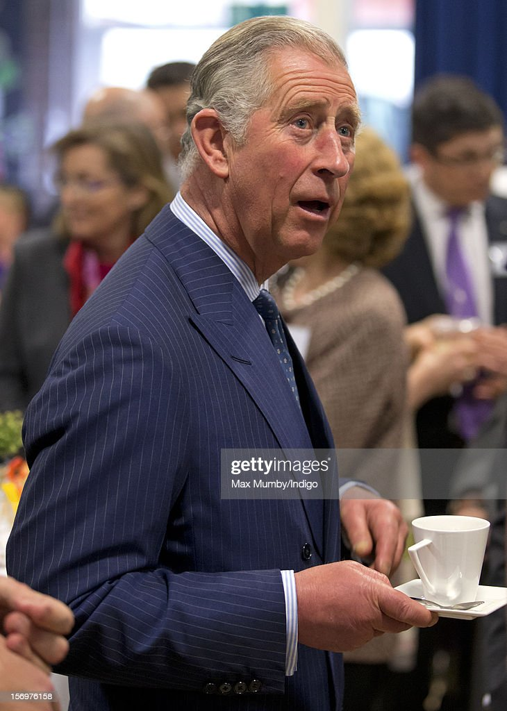 Prince Charles, Prince of Wales holds a cup and saucer as he, accompanied by Jamie Oliver, visits Carshalton Boys Sports College to see how the school has transformed its approach to healthy eating on November 26, 2012 in Carshalton, England.