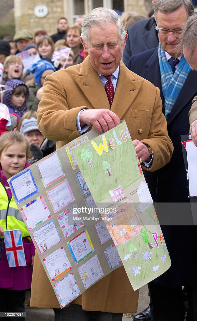 Prince Charles, Prince of Wales holds pictures and paintings given to him by local schoolchildren whilst visiting the Uley Community Stores and Post Office on February 22, 2013 in Uley, Gloucestershire, England.