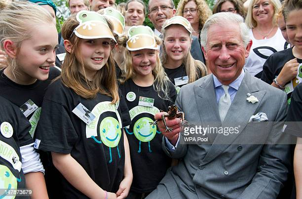 Prince Charles Prince of Wales holds with an Ecuadorian stream tree frog an endangered species discovered in the rainforests of Ecuador named...