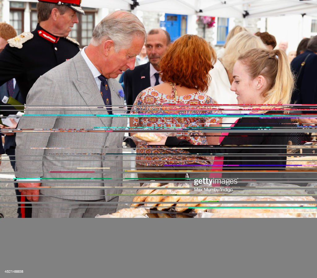 Prince Charles, Prince of Wales is presented with a Cornish Pasty as he and Camilla, Duchess of Cornwall tour a market on day one of their annual visit to Devon and Cornwall on July 14, 2014 in Looe, England.