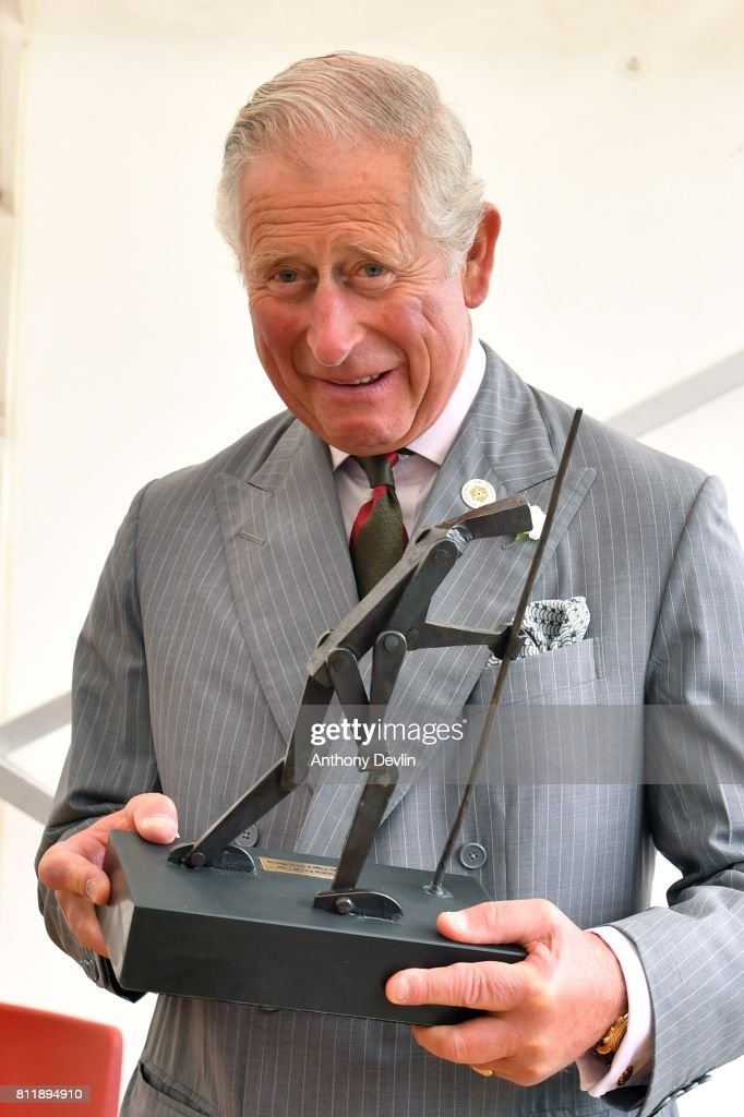 Prince Charles, Prince of Wales is presented with a sculpture by Glenn Morris as he visits the historic Strata Florida site during The Prince of Wales' annual Summer visit to Wales at Strata Florida on July 10, 2017 in Ceredigion, Wales. Strata Florida is the site of a former Cistercian monastery which was of immense importance to Wales during the Middle Ages. The conserved ruins of its church and part of the cloisters are in the care of Cadw, the Welsh Government's heritage agency, and can be visited by the public.