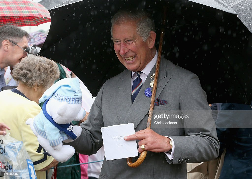 Prince Charles Prince of Wales is presented with a teddy bear for Prince George of Cambridge during a visit to the 132nd Sandringham Flower Show at...