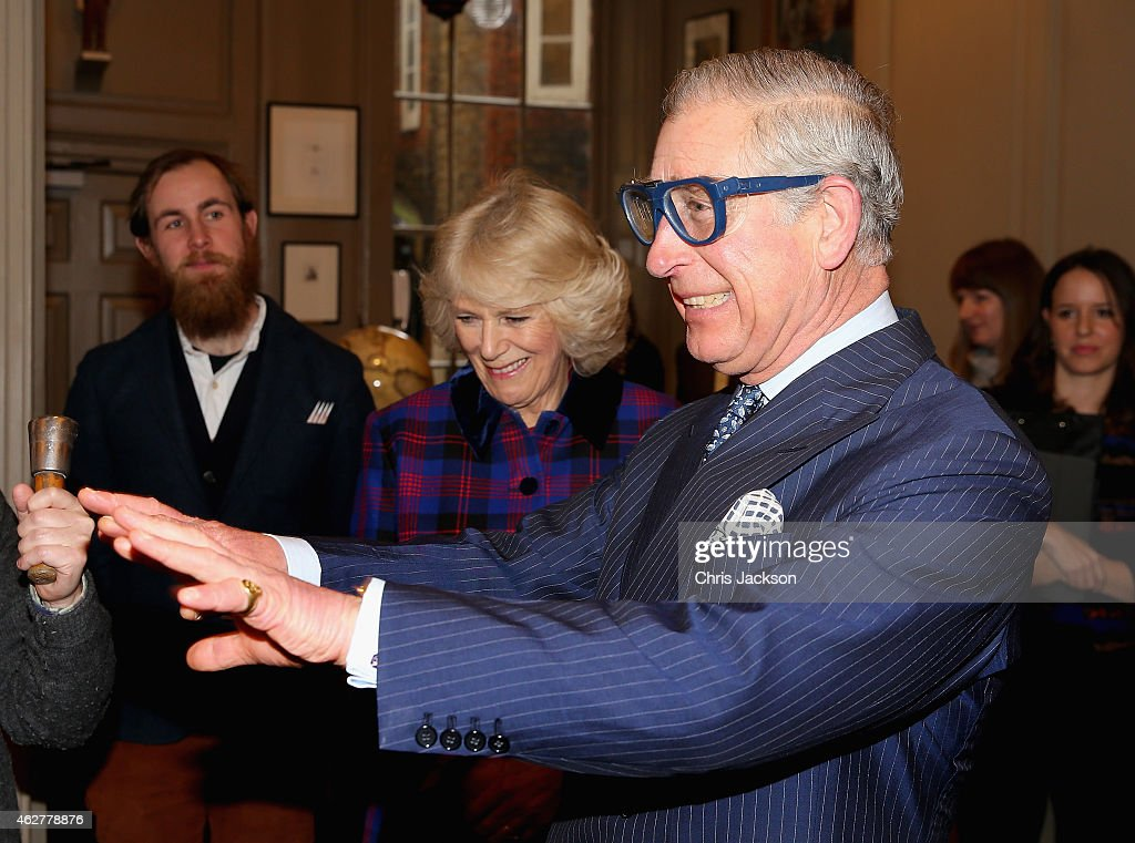 Prince Charles, Prince of Wales jokes that he can't see in a pair of safety goggles as <a gi-track='captionPersonalityLinkClicked' href=/galleries/search?phrase=Camilla+-+Hertogin+van+Cornwall&family=editorial&specificpeople=158157 ng-click='$event.stopPropagation()'>Camilla</a>, Duchess of Cornwall laughs before he tries some engraving during a visit to the Art Worker's Guild on February 5, 2015 in London, England.