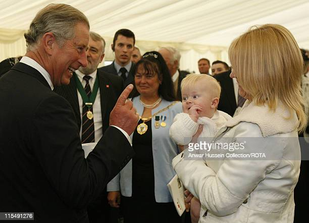 Prince Charles Prince of Wales jokes with baby Joseph Berry and his mother Jennifer following the dedication ceremony for the new National Armed...