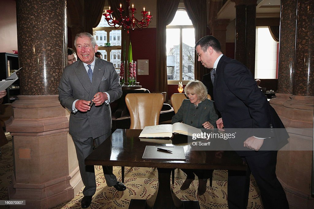Prince Charles, Prince of Wales (L) laughs as Camilla, Duchess of Cornwall signs the visitors' book as ith General Manager Kevin Kelly (R) looks on during a visit to the recently regenerated St Pancras Renaissance London Hotel adjacent to St Pancras International Station on January 30, 2013 in London, England. The Prince of Wales and The Duchess of Cornwall are marking the 150th anniversary of London Underground to emphasise the importance of engineering and infrastructure development in the UK.
