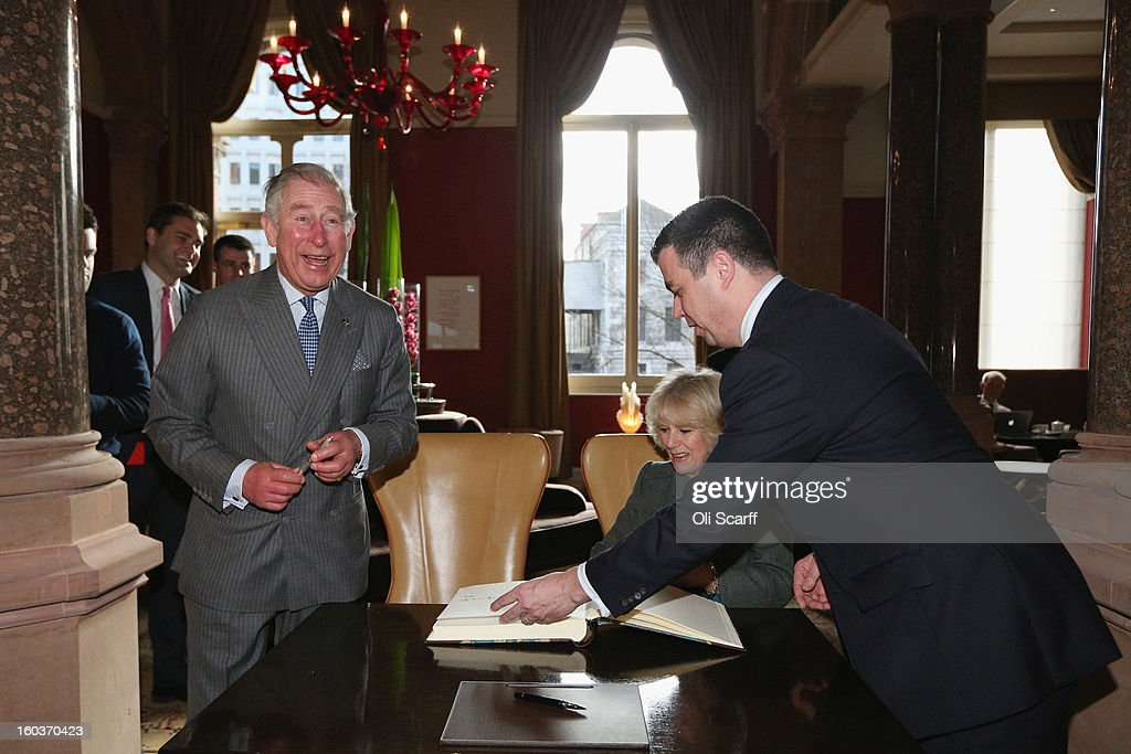 Prince Charles, Prince of Wales (L) laughs as Camilla, Duchess of Cornwall signs the visitors' book with General Manager Kevin Kelly (R)during a visit to the recently regenerated St Pancras Renaissance London Hotel adjacent to St Pancras International Station on January 30, 2013 in London, England. The Prince of Wales and The Duchess of Cornwall are marking the 150th anniversary of London Underground to emphasise the importance of engineering and infrastructure development in the UK.
