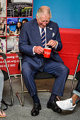 Prince Charles Prince of Wales laughs as he is given a cup of tea with two spoons in it by mistake during a visit to his Prince's Trust centre where...