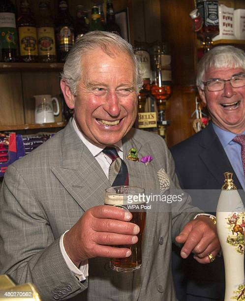 Prince Charles Prince of Wales laughs as he pulls a pint during a visit to the Glan yr Afon Arms which is supported by The Prince's Pub is the Hub...
