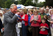 Prince Charles Prince of Wales listens as members of the Caldecote Women's Institute sing 'Jerusalem' to him during the 130th Sandringham Flower Show...