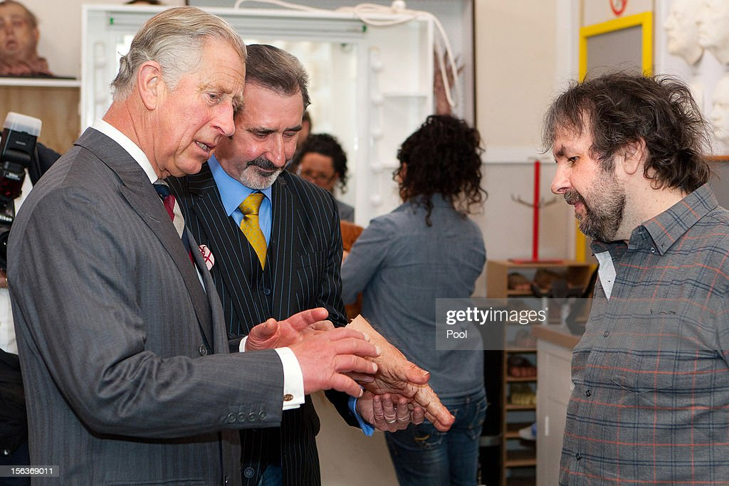 Prince Charles, Prince of Wales looks at a prostetic hand as he meets film maker Sir Peter Jackson (R) in the makeup department of Jackson's Weta Workshop on November 14, 2012 in Wellington, New Zealand. The Royal couple are in New Zealand on the last leg of a Diamond Jubilee that takes in Papua New Guinea, Australia and New Zealand.