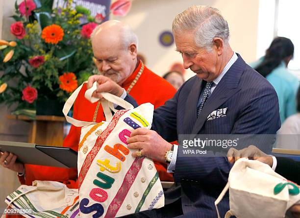 Prince Charles Prince of Wales looks at an embroidered bag a gift during a visit to St John's Church on February 10 2016 in Southall England The...